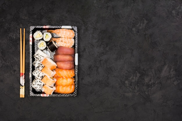 Satz gesunde asiatische rollen vereinbarte im behälter und haftet über schwarzem hintergrund Kostenlose Fotos