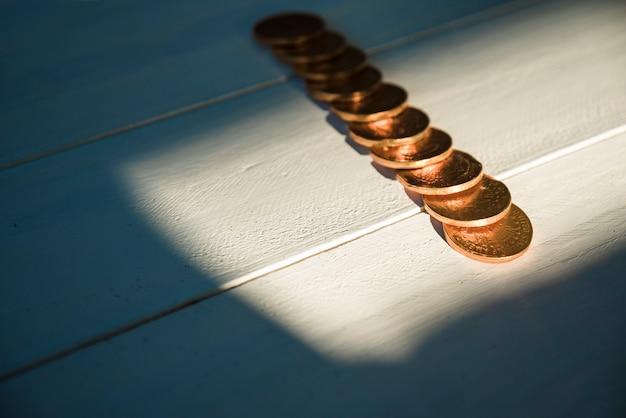 Satz goldene münzen an bord und sonnenschein in der dunkelheit Kostenlose Fotos
