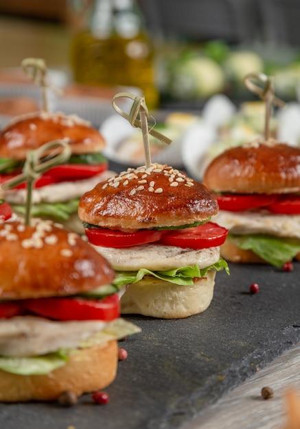 Satz hühnerburger auf schwarzem brett auf holztisch Premium Fotos