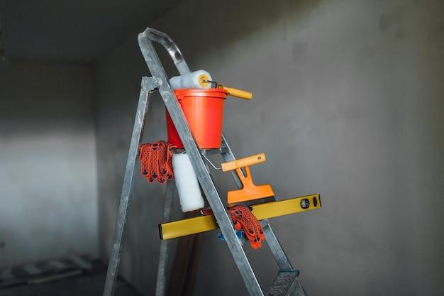 Satz instrumente für die reparatur mit unscharfem maler auf grauer wohnung Premium Fotos