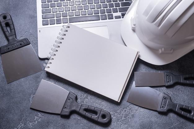 Satz kittmesser und helm auf grauem hintergrund Premium Fotos