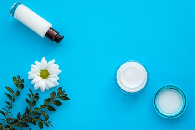 Satz kosmetikflaschen auf einem blauen hintergrund. gesichtscreme und weiße lotion mit gänseblümchenblume. naturkosmetische kräuter. Premium Fotos