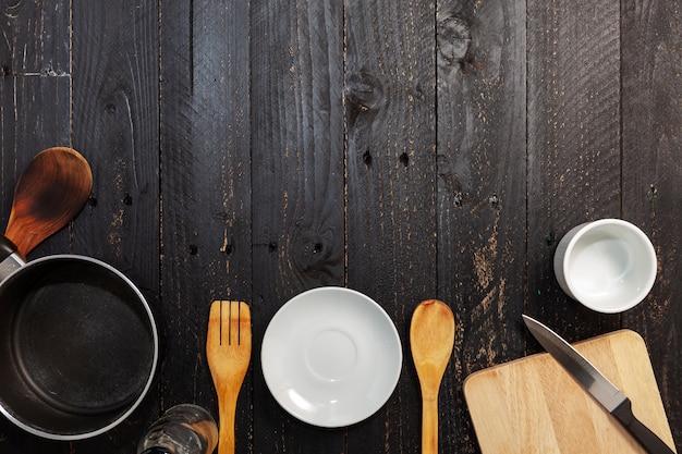 Satz küchengeschirr auf dem schwarzen hölzernen hintergrund Premium Fotos