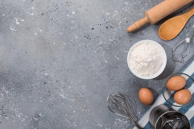Satz küchenutensilien mit produkten auf grau-blauem hintergrund. meisterkurse kochen. speicherplatz kopieren. Premium Fotos