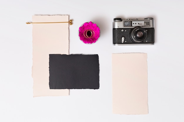 Satz papiere nahe frischer blume mit ringen auf platte und retro- kamera Kostenlose Fotos