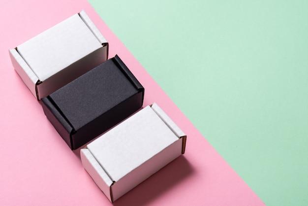 Satz schwarzweiss-kartonschachteln auf grünem und rosa tisch, draufsicht, kopienraum Premium Fotos