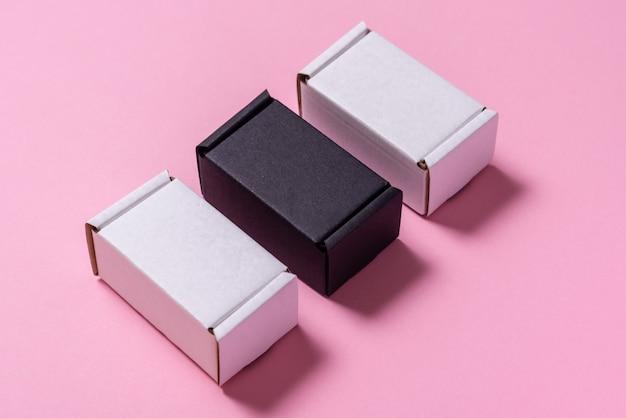 Satz schwarzweiss-kartonschachteln auf rosa tisch, draufsicht, flache lage Premium Fotos