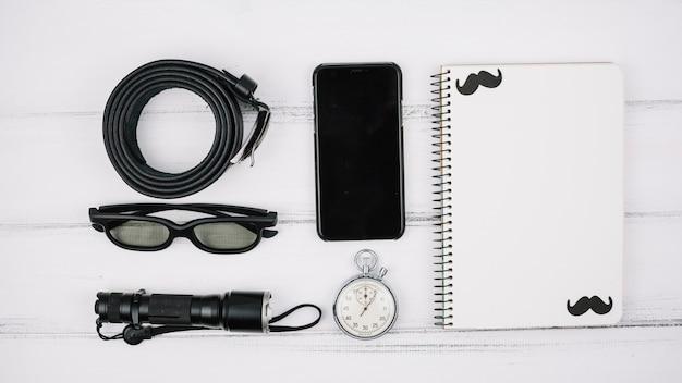 Satz smartphone nahe notizbuch und männlichem zubehör Kostenlose Fotos