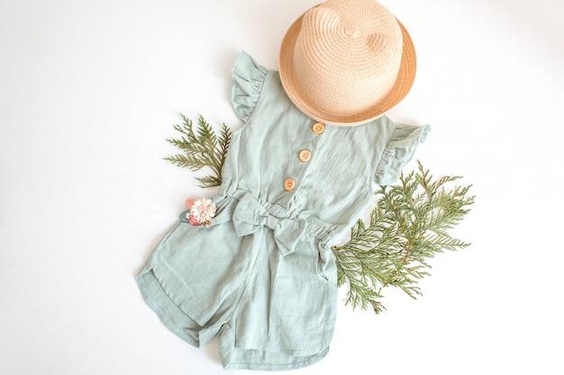 Satz sommerkinderkleidung für mädchen, stilvollen spielanzug, strohhut und blumenzusatz. Premium Fotos