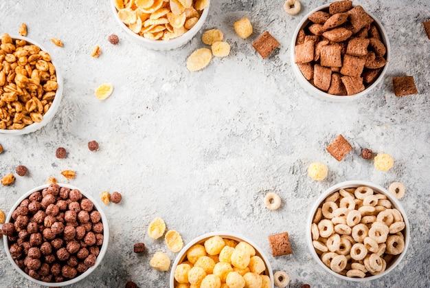 Satz verschiedene frühstückskost aus getreide corn flakes, hauche, knalle, grauer draufsichtrahmen des steintabellenkopienraumes Premium Fotos