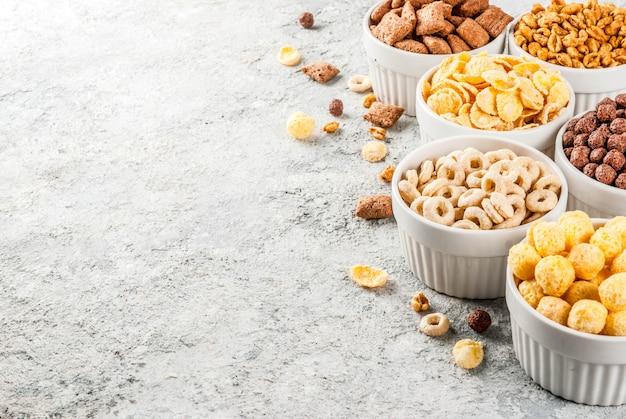 Satz verschiedene frühstückskost aus getreide corn flakes, hauche, knalle, grauer steintabellen-kopienraum Premium Fotos