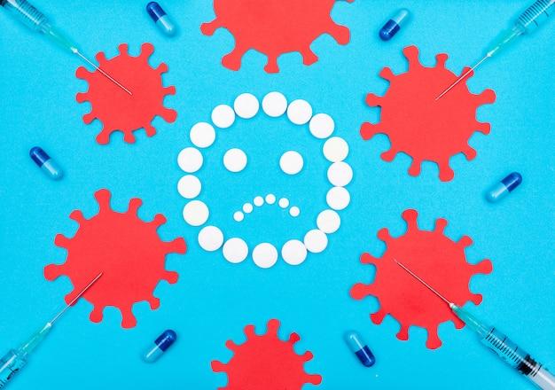 Satz virus in der nähe und pillen bilden traurige emoji mit nadeln und pillen Kostenlose Fotos