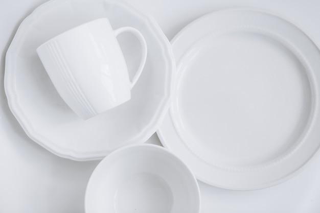 Satz weiße geräte von drei verschiedenen platten und eine tasse in einem teller Kostenlose Fotos