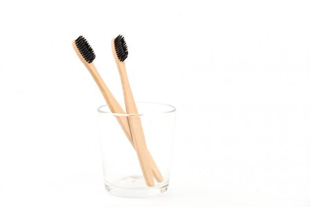Satz zahnbürsten im glas lokalisiert auf weißem hintergrund. bambus umweltfreundlich. kein verlust Premium Fotos