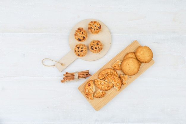 Satz zimt und verschiedene kekse auf einem schneidebrett auf einer weißen oberfläche Kostenlose Fotos