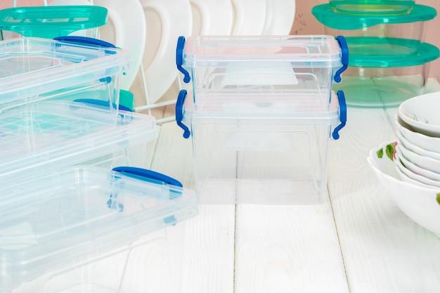 Saubere küche mit verschiedenen tellern und nahrungsmittelkästen Premium Fotos