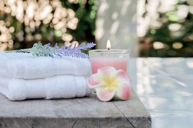 Saubere tücher der nahaufnahme mit rosa kerze und blume auf holztisch Premium Fotos
