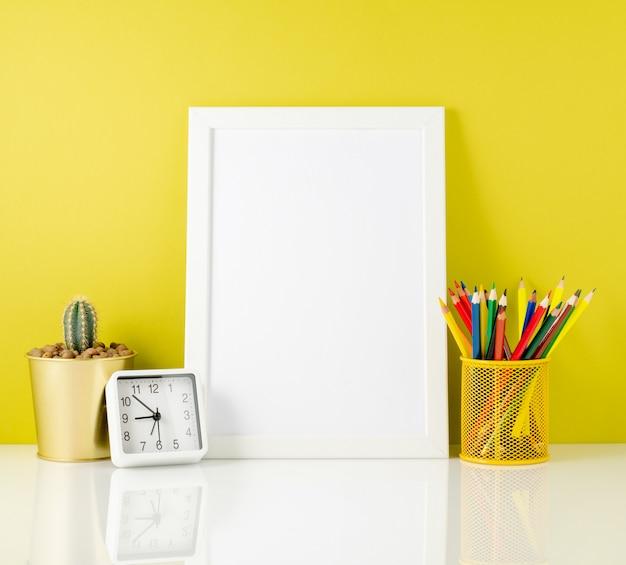 Sauberer weißer rahmen des modells, farbige bleistifte auf dem hellen gelben hintergrund Premium Fotos