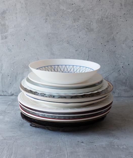 Sauberes geschirr auf dem tisch in einem stapel auf einem grauen hintergrund Premium Fotos