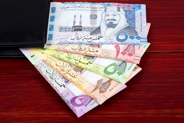 Saudi-rial-banknoten in der schwarzen geldbörse Premium Fotos