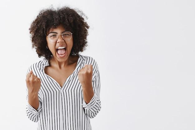 Sauer verärgert afroamerikanische weibliche büroleiterin in gestreifter bluse und brille geballte fäuste mit wütenden gefühlen schreien und zeigen, krank und müde von dummen kollegen zu sein Kostenlose Fotos