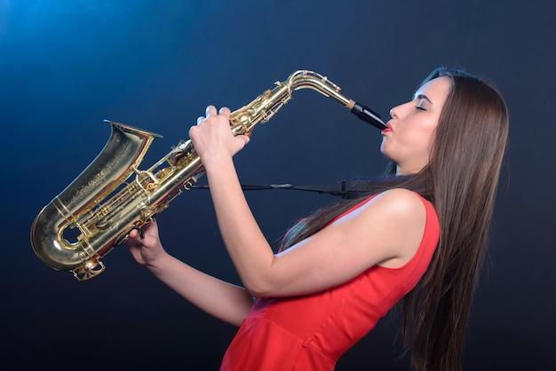 Saxophonistfrau im roten kleid Premium Fotos
