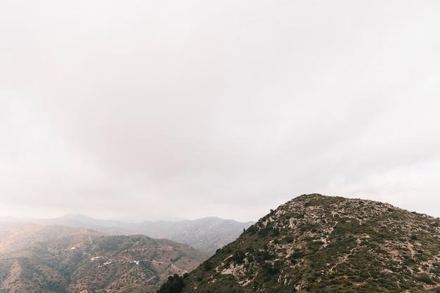 Scenics-ansicht der felsigen berglandschaft mit weißem bewölktem himmel Kostenlose Fotos