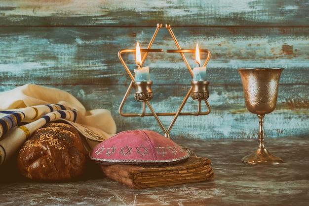 Schabbat-tischkerzen und eine tasse wein mit bedecktem challa-brot, Premium Fotos