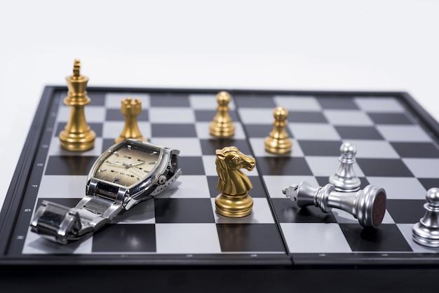 Schachbrett auf weißen, goldenen und silbernen zahlen mit handuhr Premium Fotos
