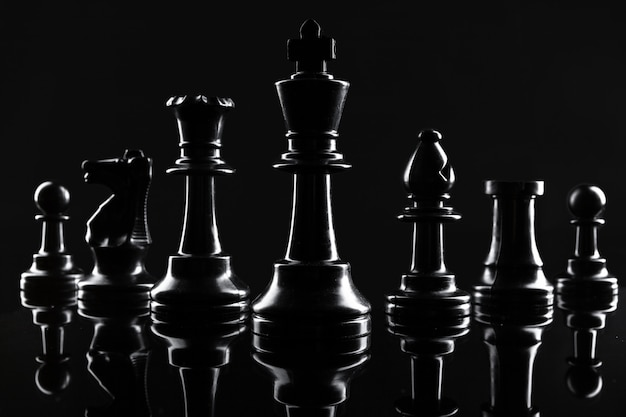 Schachfiguren auf hintergrundabschluß des dunklen schwarzen oben Premium Fotos