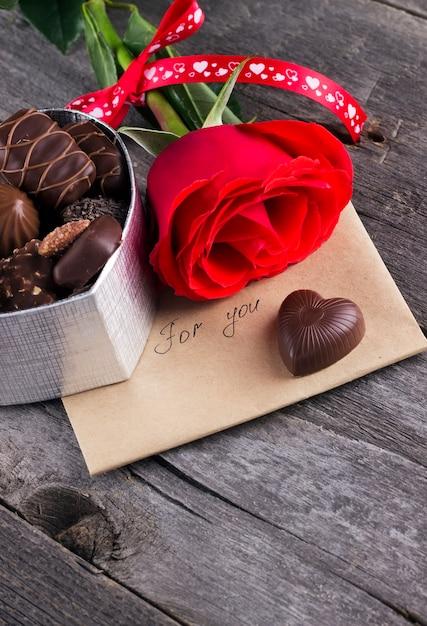 Schachtel pralinen, rote rose auf einem dunklen hintergrund Premium Fotos