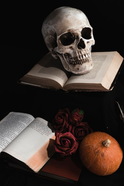 Schädel auf büchern mit rosen und kürbis Kostenlose Fotos