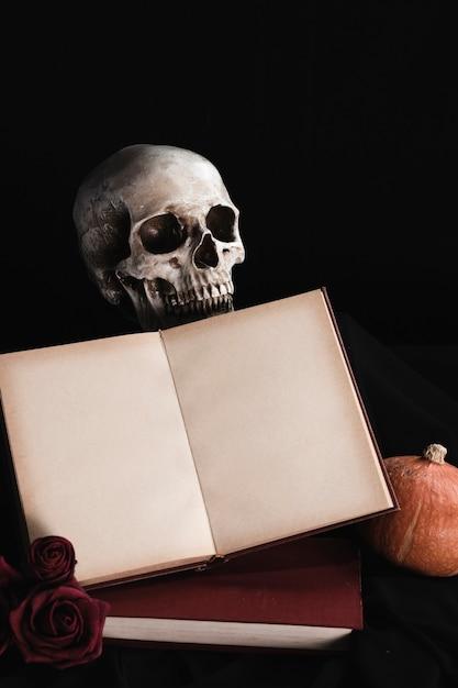 Schädel mit buchmodell auf schwarzem hintergrund Kostenlose Fotos