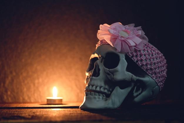 Schädelstillleben menschlicher schädel mit dem rosa stirnband herum verziert an der halloween-partylichtkerze Premium Fotos