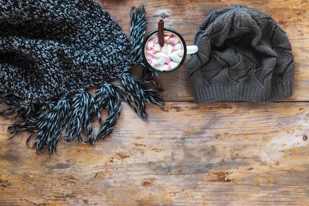 Schal und hut in der nähe von heißer schokolade Kostenlose Fotos