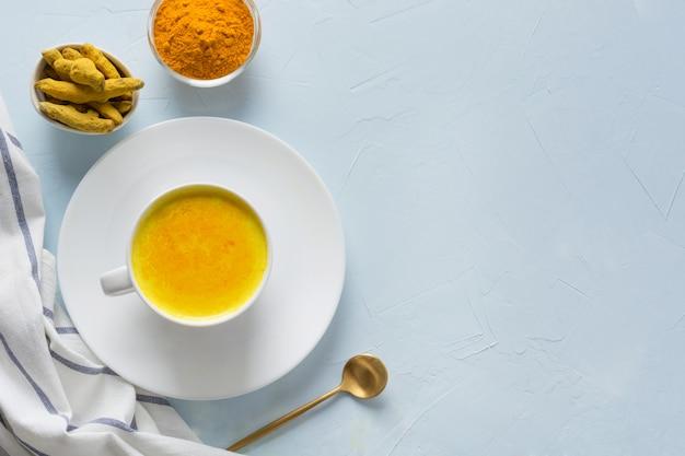 Schale ayurvedische goldene gelbwurzmilch mit honig auf blau. exemplar oder rezept. gesundes getränk für die immunität. ansicht von oben. natürliches essen Premium Fotos