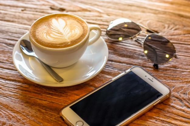 Schale des lattekunstkaffees mit löffel und platte auf der braunen barke schön mit dem warmen licht verziert mit sonnenbrille und handy Premium Fotos