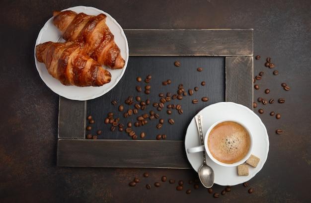 Schale frischer kaffee mit hörnchen auf dunkelheit. Premium Fotos