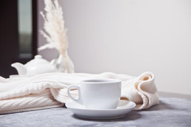 Schale heißer aromakaffee und weißes plaid des knittead und weiße teekanne auf der grauen tabelle Premium Fotos