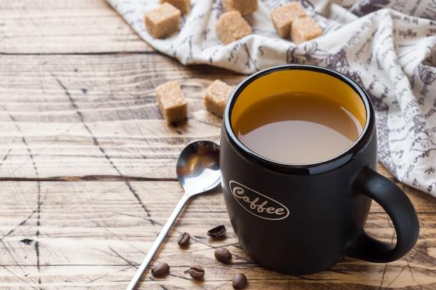 Schale heißer dämpfender schwarzer kaffee mit zuckerwürfeln auf holztisch Premium Fotos