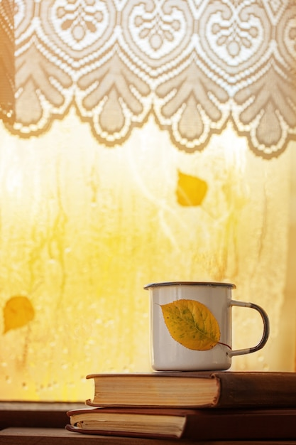 Schale herbsttee oder -kaffee und gelbblätter auf regnerischem fenster Premium Fotos