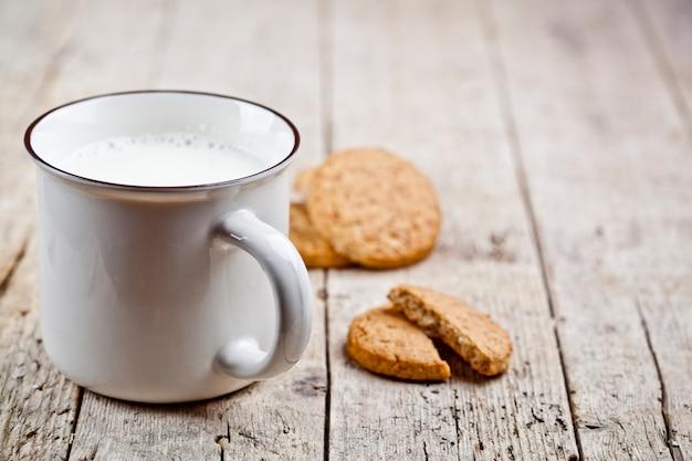 Schale milch und einige frische gebackene haferplätzchen auf rustikalem holztisch Premium Fotos