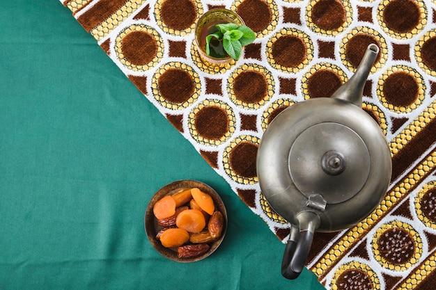 Schale nahe retro- teekanne und trockenfrüchten nahe matte auf geknittertem material Kostenlose Fotos