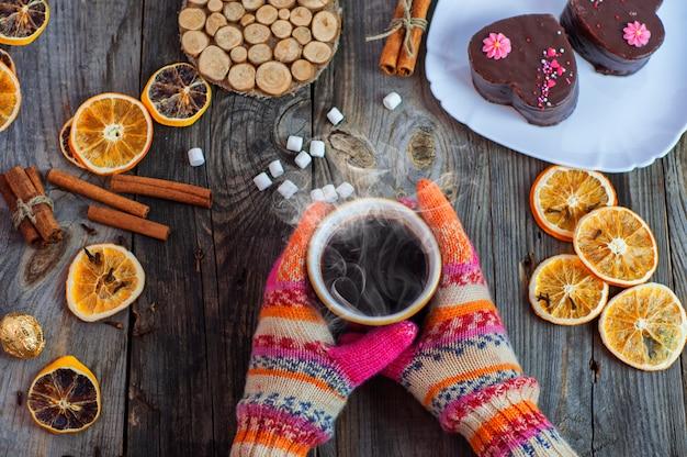 Schale schwarzer heißer kaffee in ihren händen, bunte winterhandschuhe auf händen tragend Premium Fotos
