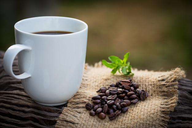 Schale schwarzer kaffee und kaffeebohnen auf hölzernem hintergrund. Premium Fotos