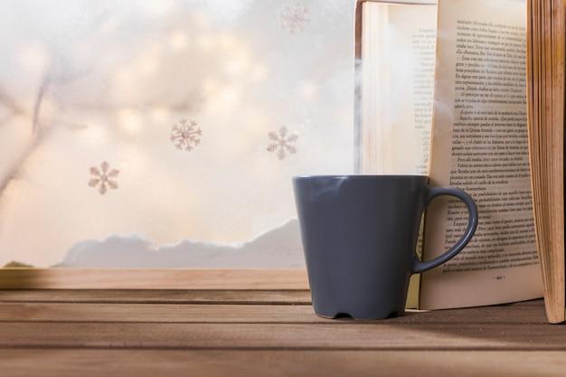 Schale und buch auf hölzerner tabelle nahe bank des schnees und der schneeflocken Kostenlose Fotos