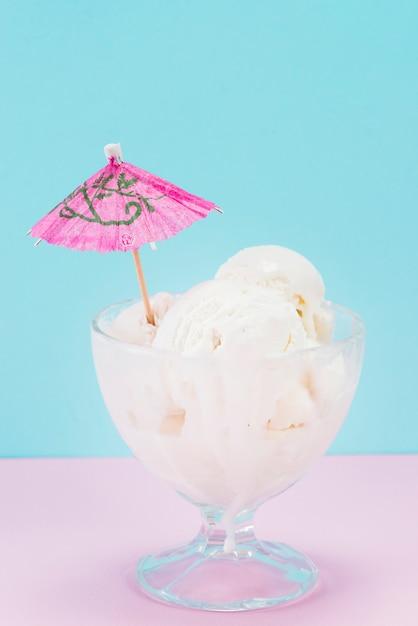 Schale vanilleeis mit papierregenschirm auf die oberseite Kostenlose Fotos