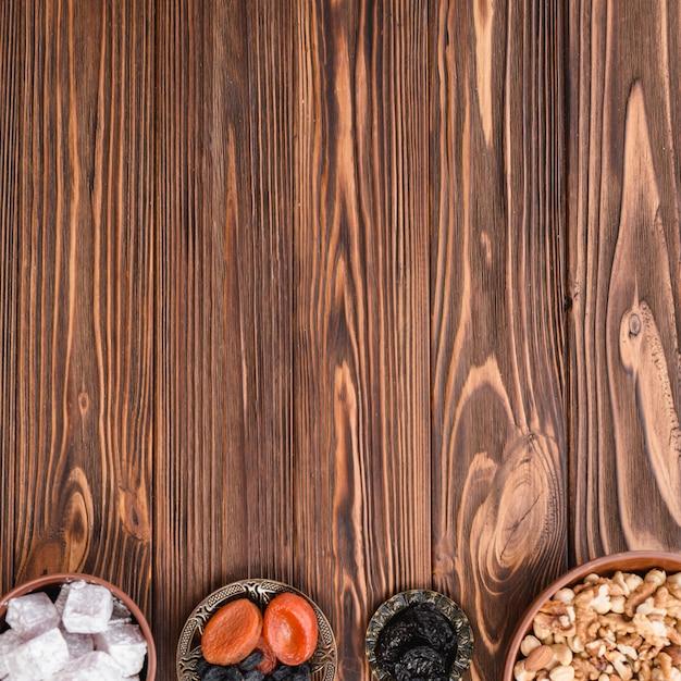 Schalen mit lukum; erdnüsse und trockenfrüchte auf dem hölzernen hintergrund mit kopienraum für das schreiben des textes Kostenlose Fotos