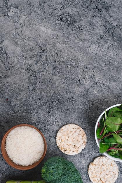Schalen mit reiskörnern; puffreiskuchen; brokkoli und spinat auf grauem verwittertem hintergrund Kostenlose Fotos