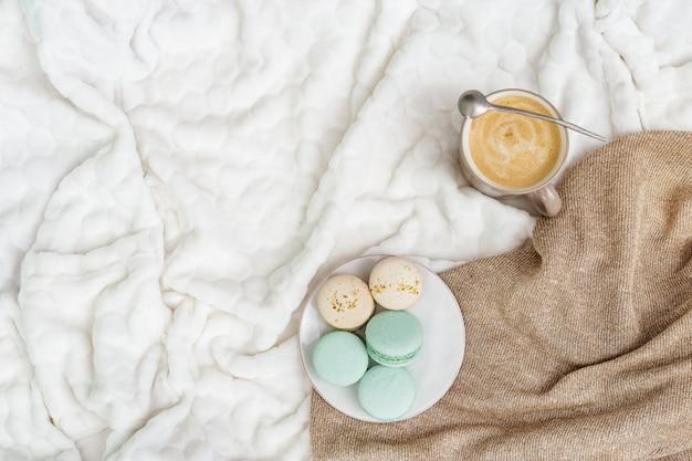 Schalenkaffeecappuccino und geschmackvolle süße makronen auf hellem hintergrund mit kopienraum. wintermorgenkonzept, zeit für sich zu entspannen. ansicht von oben. flach liegen Premium Fotos
